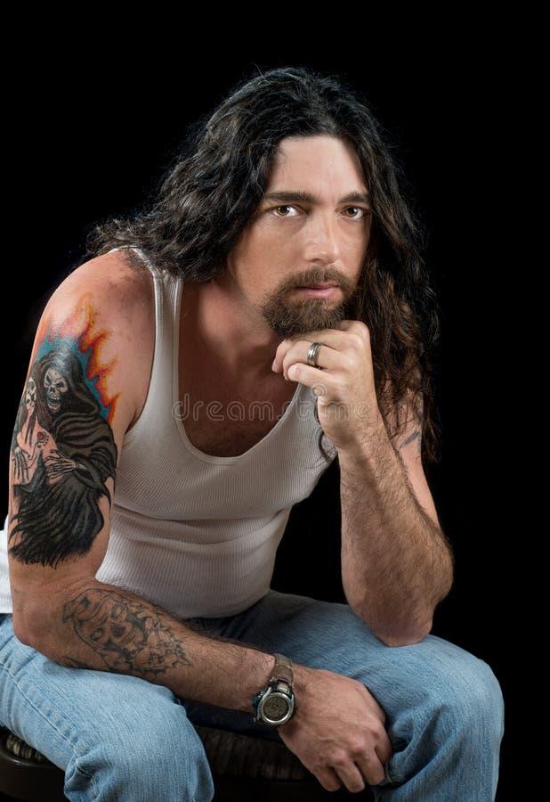 Twardy Seksowny mężczyzna z długim ciemnym włosy i pięknymi brown oczami obrazy stock