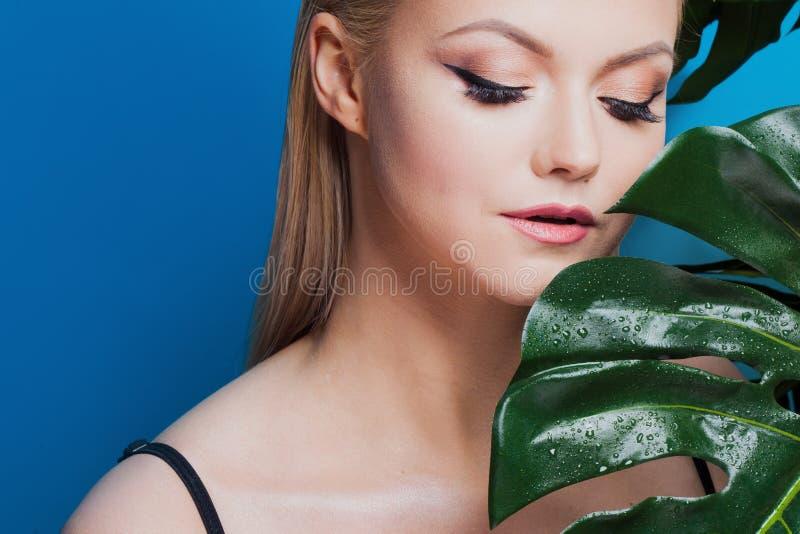 Twarz atrakcyjna młoda blondynka i liście drzewka palmowe Młoda kobieta w błękitnym bikini na błękitnym tle obrazy stock