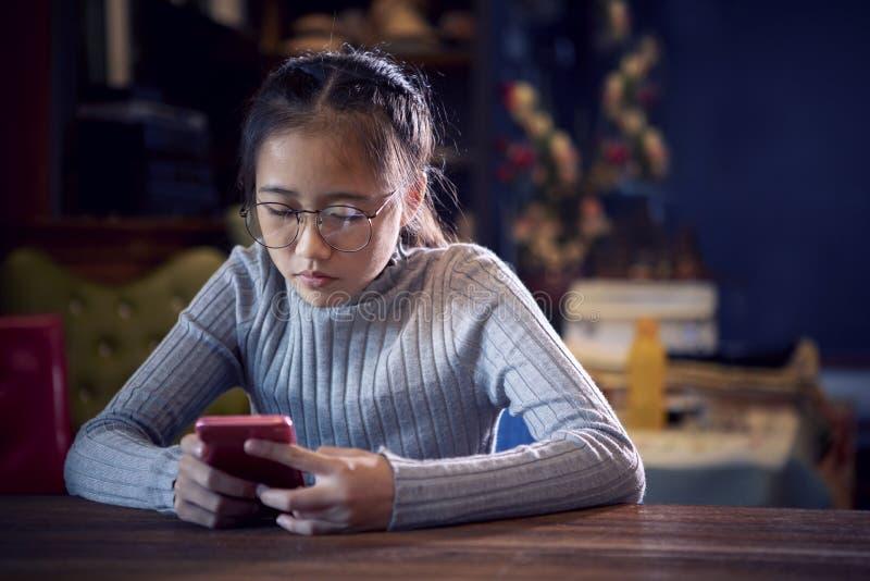 Twarz azjatykciego nastolatka czytelnicza wiadomość na mądrze telefonie w domowym li zdjęcia stock