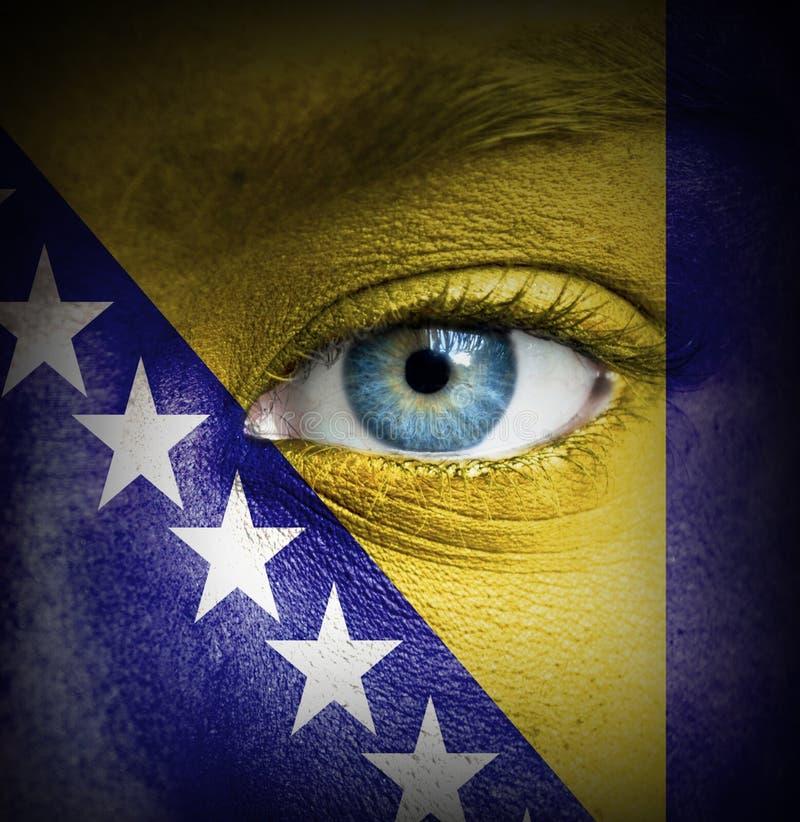 Twarz ludzka malował z flagą Bośnia i Herzegovina zdjęcie stock