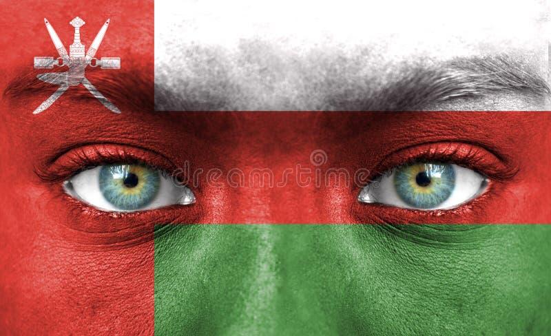 Twarz ludzka malująca z flagą Oman zdjęcie royalty free