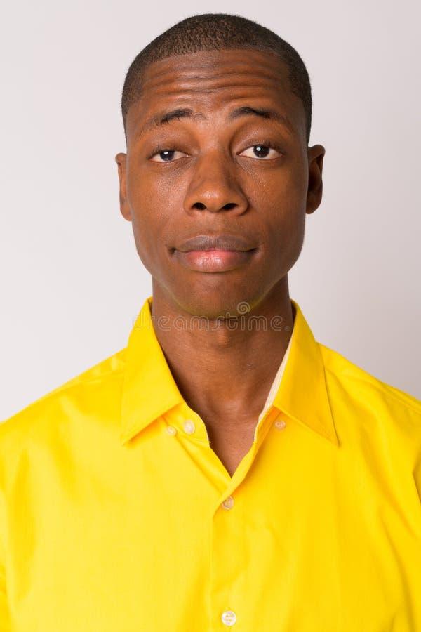 Twarz młody przystojny łysy Afrykański biznesmen jest ubranym żółtą koszula zdjęcie royalty free