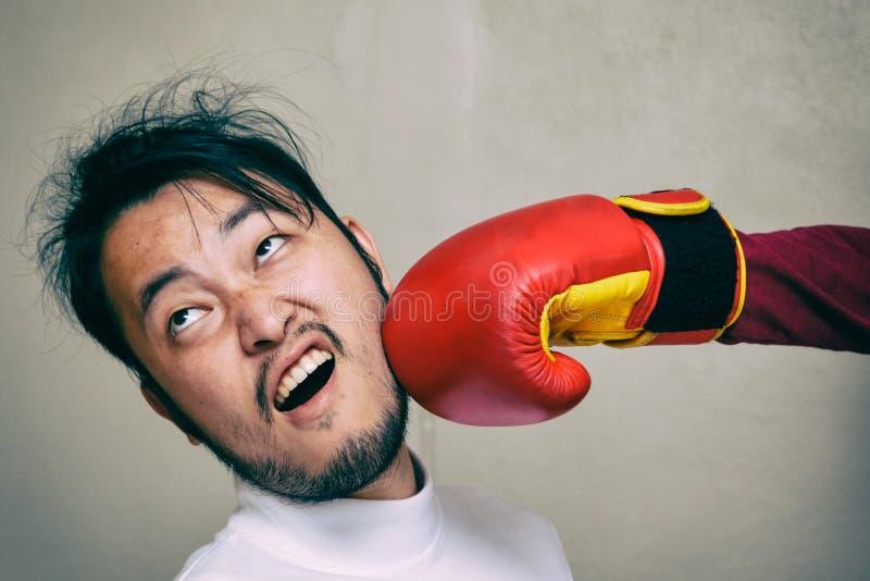 Twarz mężczyzna dostaje poncz w twarzy z bokserską rękawiczką przeciw g obrazy stock