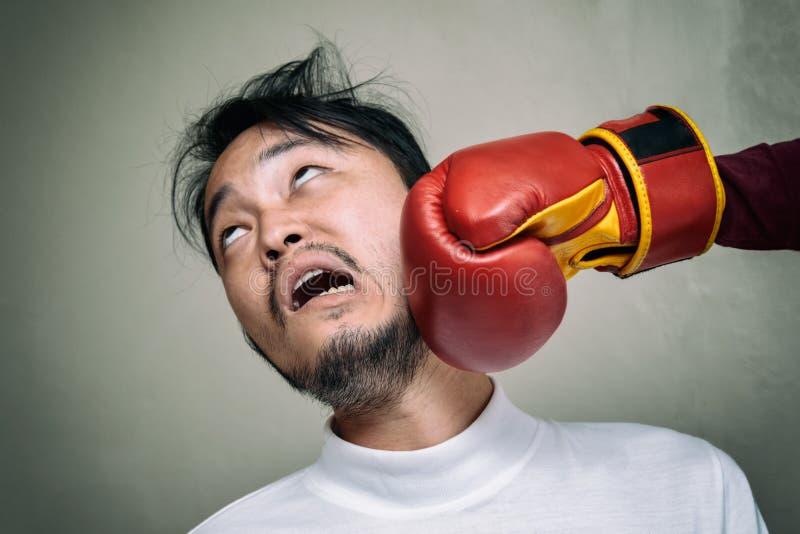 Twarz mężczyzna dostaje poncz w twarzy z bokserską rękawiczką przeciw g zdjęcia stock