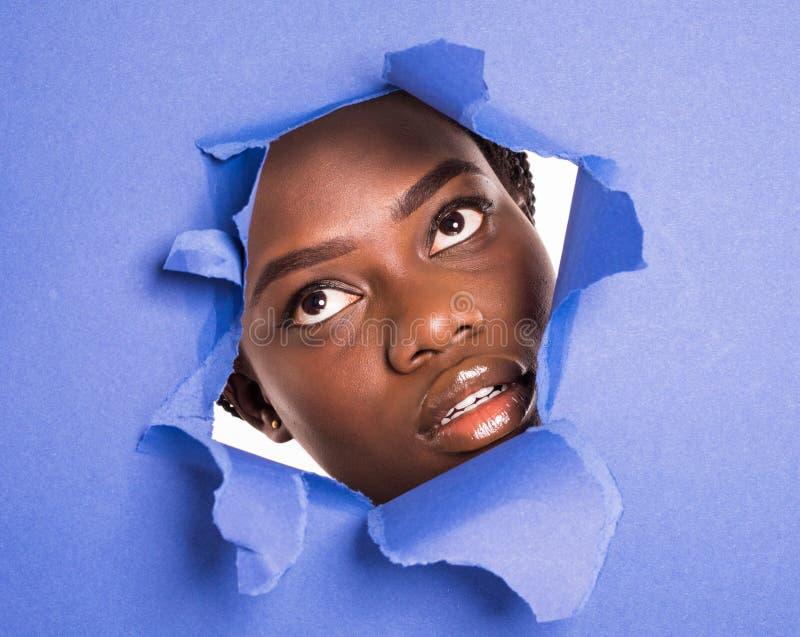 Twarz młoda piękna afrykańska dziewczyna z jaskrawym makijażem bufiastymi purpurowymi wargami i ono przygląda się w dziurę w fioł fotografia royalty free