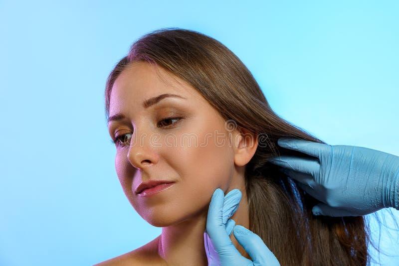 Twarz pięknej dziewczyny z rękami lekarza w rękawiczkach medycznych, odizolowana na niebieskim tle obraz stock