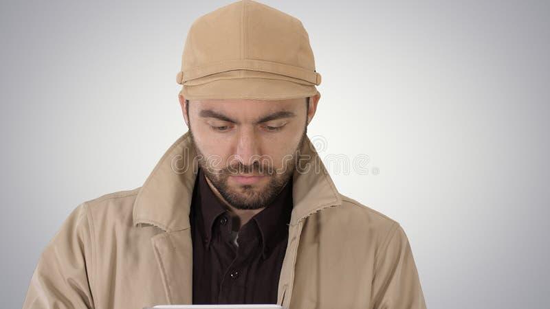 Twarz przystojny mężczyzna używa cyfrową pastylkę na gradientowym tle zdjęcia royalty free