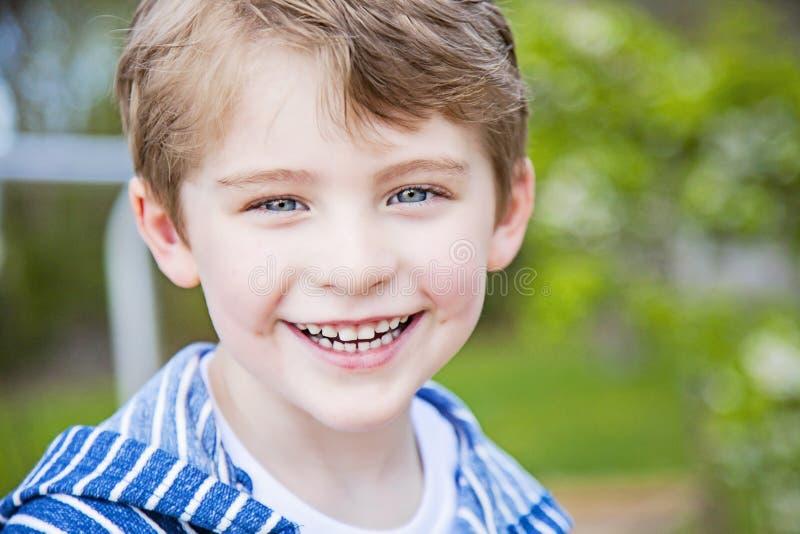 Twarz uśmiechnięta szczęśliwa chłopiec outside zdjęcie royalty free