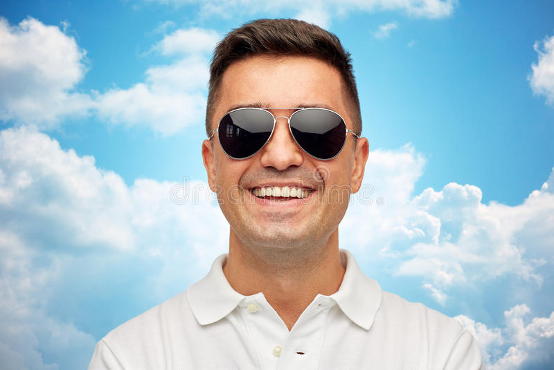 Twarz uśmiechnięty mężczyzna w okularach przeciwsłonecznych nad niebieskim niebem fotografia royalty free