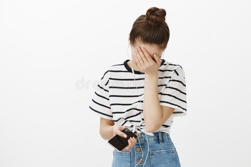 Twarzy palma od głupich pieśniowych liryka Portret zdewastowana wzburzona młoda kobieta z babeczki fryzurą, zakrywa twarz z ręką fotografia royalty free