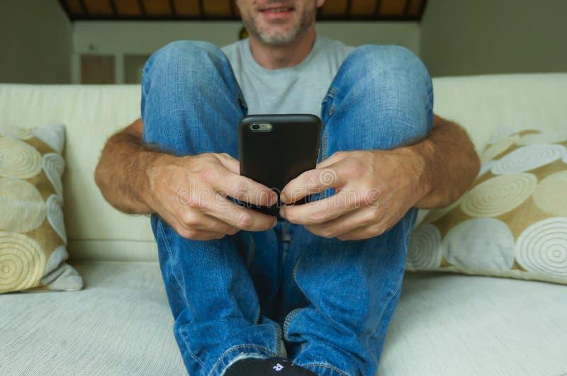 Twarzy uprawy stylu życia portret z zakończenie rękami młody szczęśliwy mężczyzna mienia telefonu komórkowego obsiadanie up relak zdjęcia royalty free