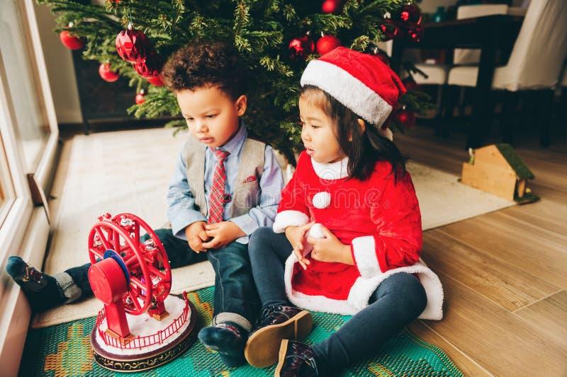 Twee aanbiddelijke 3 éénjarigenjonge geitjes die door de Kerstboom spelen royalty-vrije stock afbeeldingen