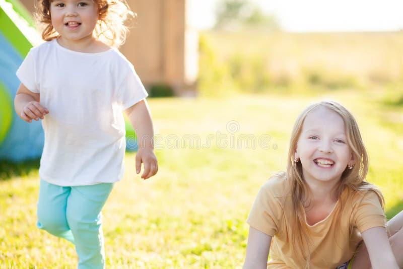 Twee aanbiddelijke kleine zusters die pret hebben bij de binnenplaats royalty-vrije stock foto