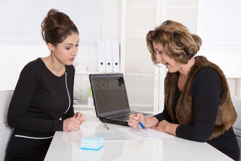 Twee aantrekkelijke bedrijfscollega's die bij bureau bij o samenwerken stock foto's