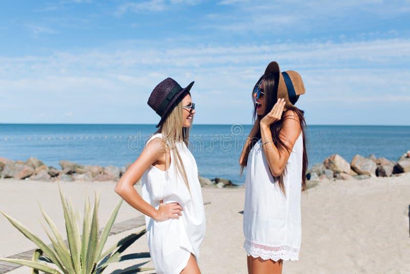 Twee aantrekkelijke donkerbruine en blonde meisjes met lang haar bevinden zich op het strand dichtbij overzees Zij dragen hoeden, royalty-vrije stock foto's