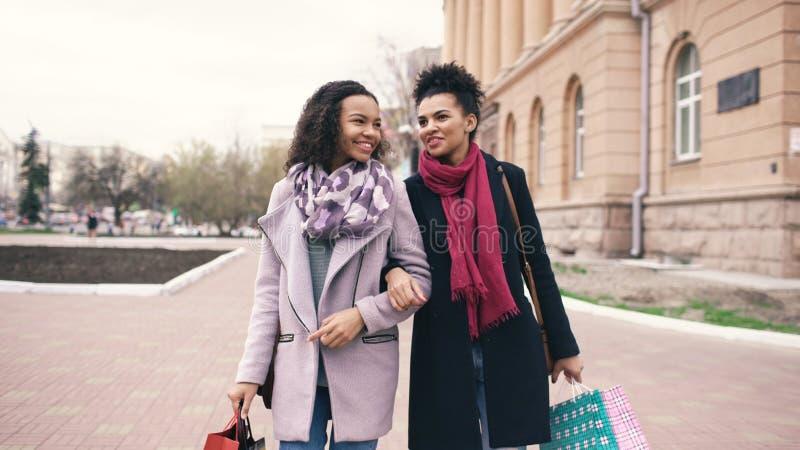 Twee aantrekkelijke gemengde rasvrouwen met het winkelen doet het spreken in zakken en het lopen onderaan de straat De meisjes he stock foto's