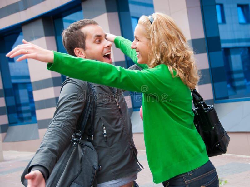 Twee aantrekkelijke jonge mensen kwamen in de straat samen stock afbeeldingen