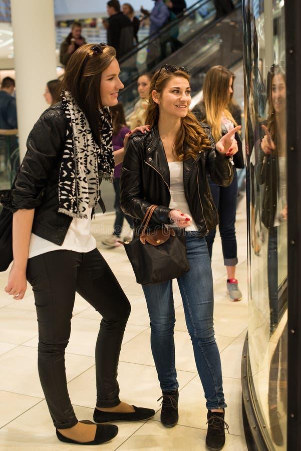 Twee aantrekkelijke jonge vrouwen die door winkel kijken royalty-vrije stock foto