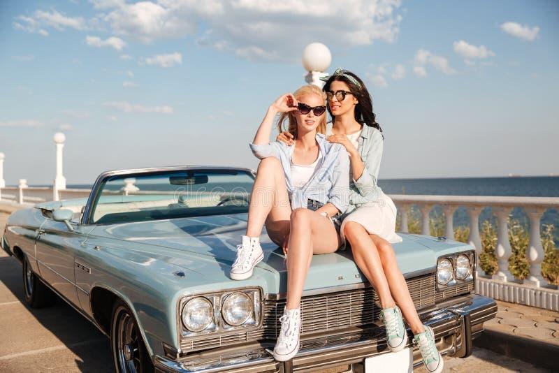 Twee aantrekkelijke jonge vrouwen die op auto zitten stock foto