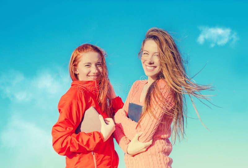 Twee aantrekkelijke meisjes die pret hebben die in openlucht van verse lucht op winderige de zomerdag genieten royalty-vrije stock afbeeldingen