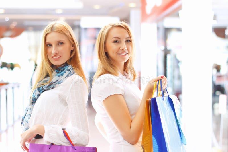 Twee aantrekkelijke meisjes die uit winkelen royalty-vrije stock foto