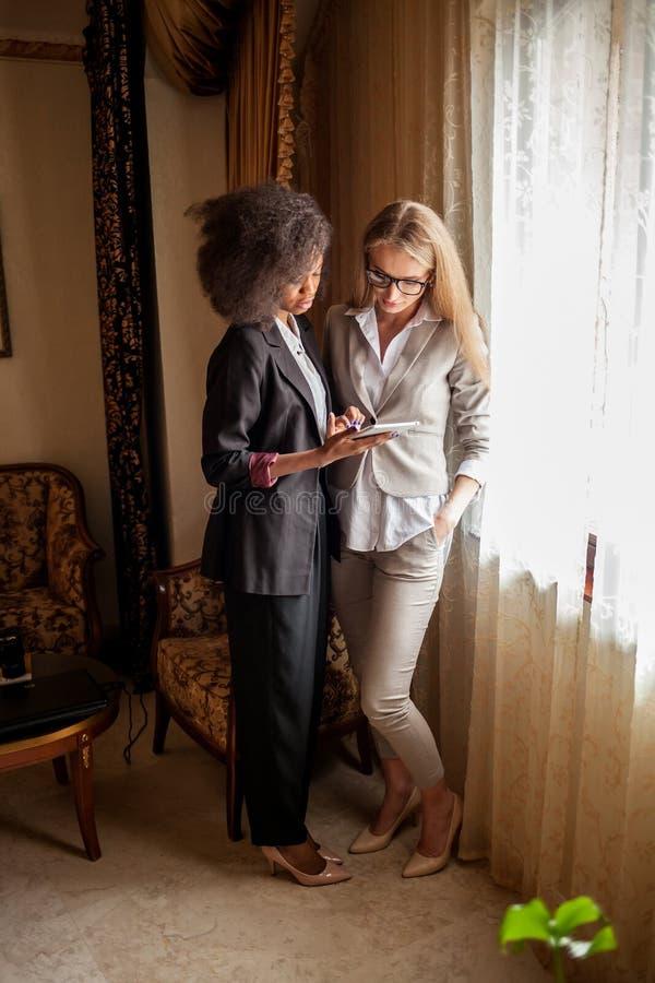 Twee aantrekkelijke modieuze onderneemsters in kostuums werken aan de tablet dichtbij het venster in luxebureau stock foto's