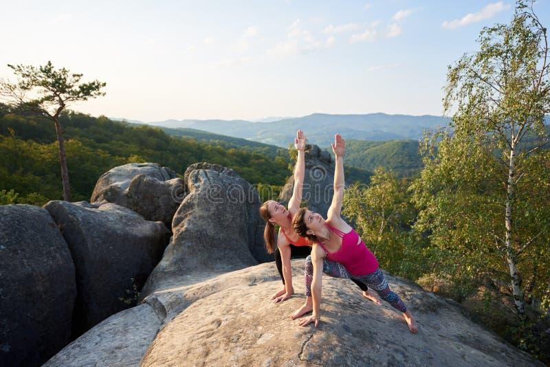 Twee aantrekkelijke slanke vrouwen die ingewikkelde yoga doen stellen op aangestoken door de bovenkant van de de zomerzon van reu royalty-vrije stock foto