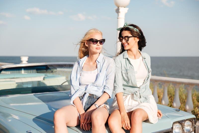 Twee aantrekkelijke vrouwen die op de auto in de zomer zitten royalty-vrije stock foto