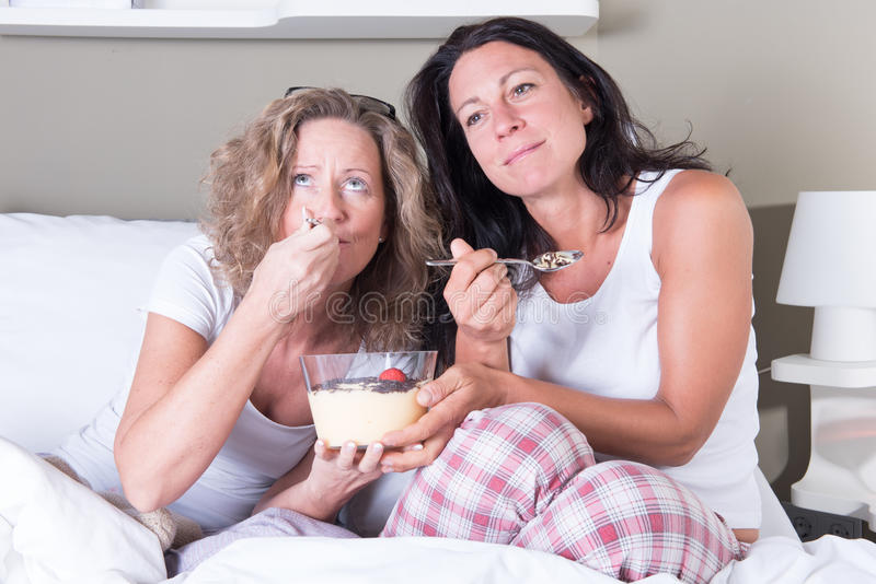 Twee aantrekkelijke vrouwen die van de avond van hun vrouwen in bed genieten stock fotografie