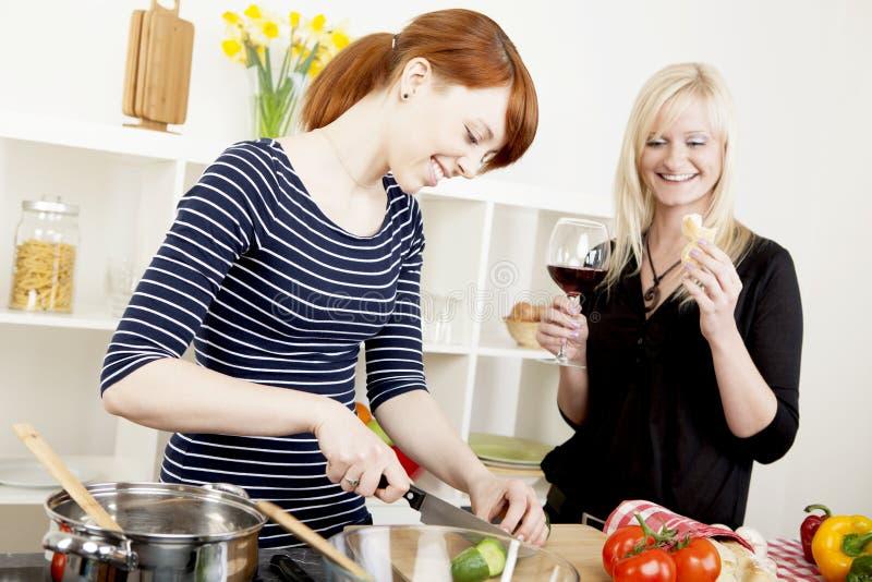 De vrienden die van vrouwen een maaltijd voorbereiden stock fotografie