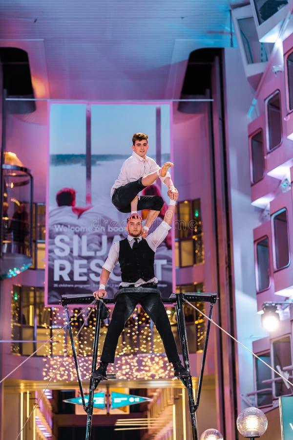 Twee acrobaten die op het Promanade-dek van lidstaten Silja Serenade van Silja Line presteren stock afbeeldingen