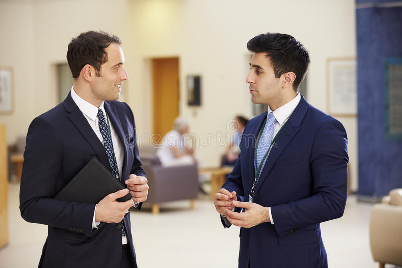 Twee Adviseurs die Vergadering in het Ziekenhuisontvangst hebben royalty-vrije stock afbeelding