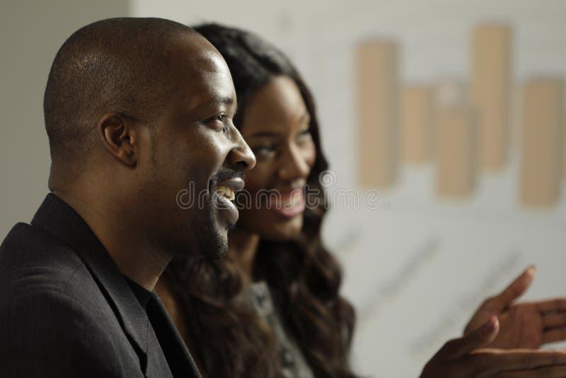 Twee Afrikaanse Amerikaanse bedrijfsman en vrouw in een vergadering stock foto's