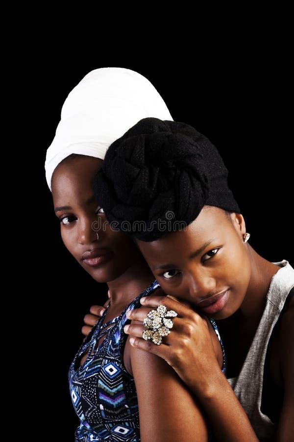 Twee Afrikaanse Amerikaanse zusters in hoofddoek op donkere achtergrond royalty-vrije stock afbeelding