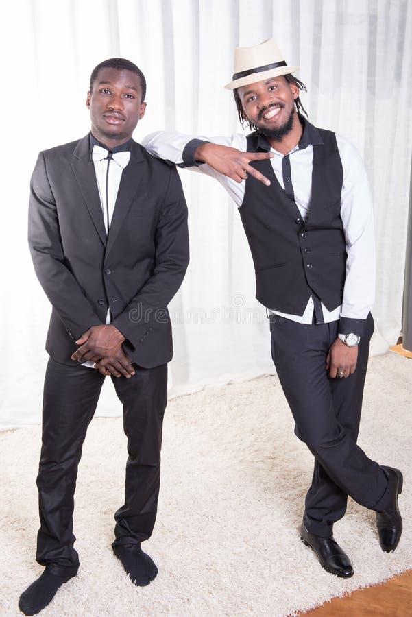 Twee Afrikaanse kerels die op een tapijt stellen stock afbeeldingen