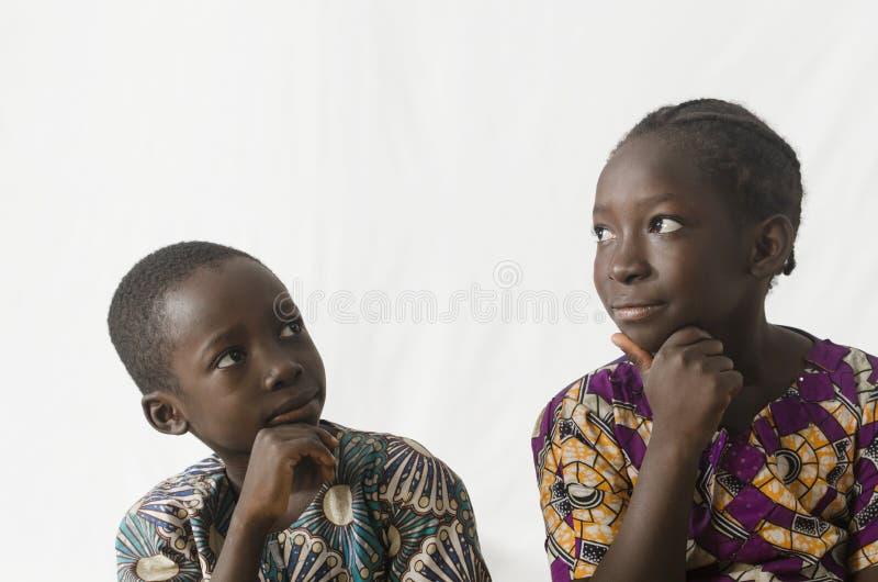 Twee Afrikaanse kinderen die met handen op hun kinnen denken, isoleren stock afbeelding