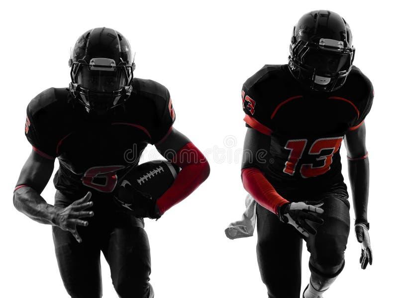 Twee Amerikaanse voetbalsters die silhouet in werking stellen royalty-vrije stock afbeelding
