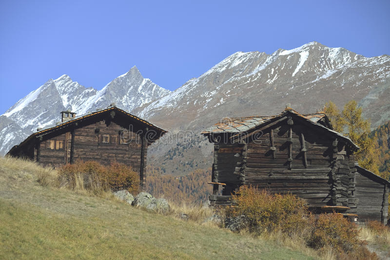 Twee antieke blokhuizen van oud dorp van Zermatt met Matterhorn-piek op achtergrond stock afbeeldingen