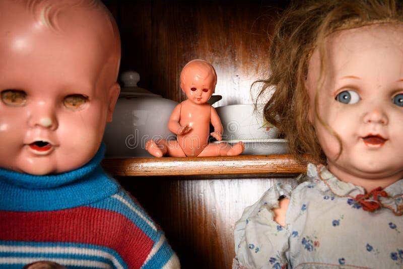 Twee antieke kindpoppen met een baby - pop tussen hen op de achtergrond stock foto's