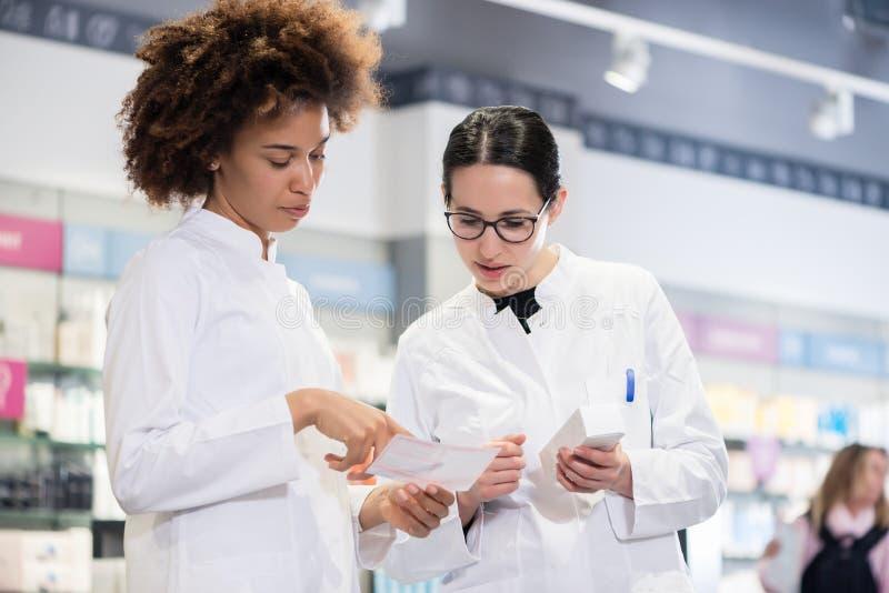 Twee apothekers die geneesmiddelen betreffende aanwijzingen en bijwerkingen vergelijken stock afbeelding