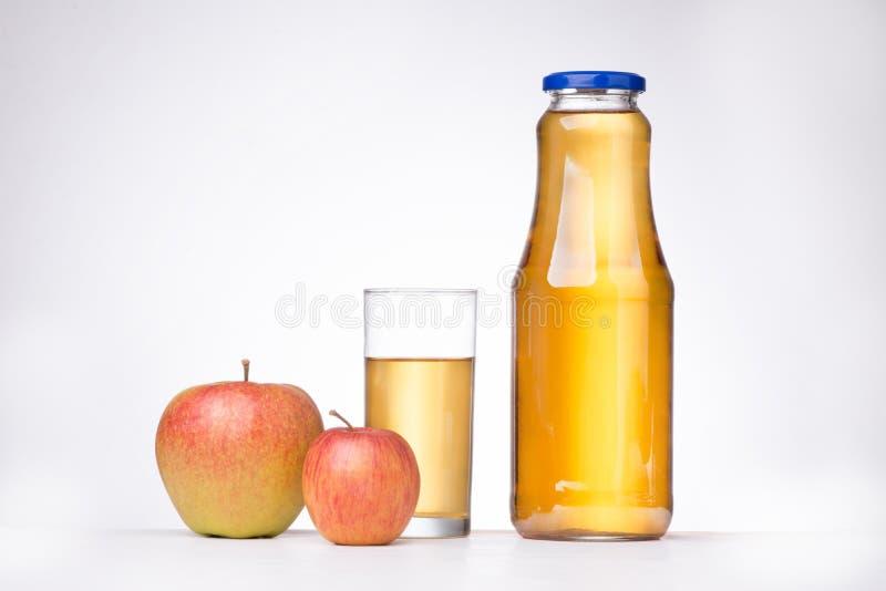Twee appelen en een fles appelsap op witte achtergrond royalty-vrije stock afbeeldingen