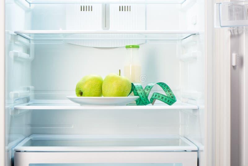 Twee appelen met het meten van band en glasfles in ijskast royalty-vrije stock foto