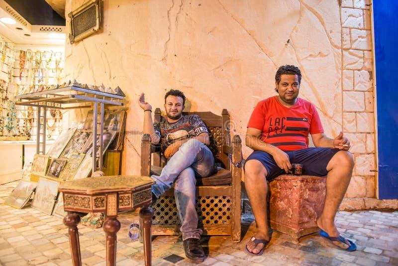 Twee Arabische mensen die en thee rusten drinken bij de straat van de nachtstad stock foto