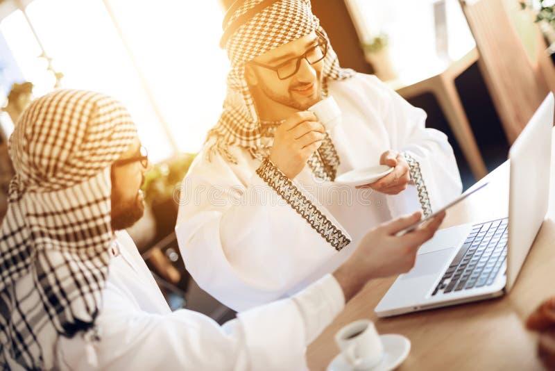 Twee Arabische zakenlieden die koffie drinken bij lijst bij hotelruimte stock foto's
