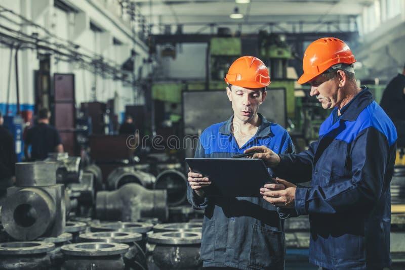 Twee arbeiders bij een bedrijf met een in hand tablet, workin royalty-vrije stock afbeelding