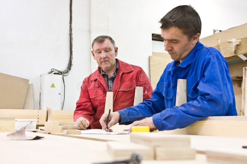 Twee arbeiders bij een houten werkbank stock afbeeldingen