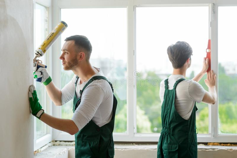 Twee arbeiders die een venster installeren royalty-vrije stock foto