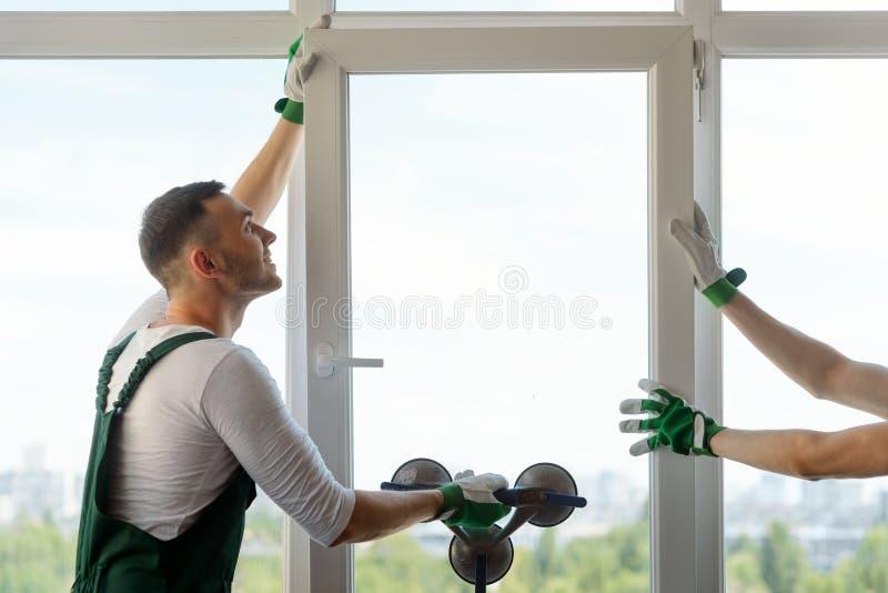 Twee arbeiders die een venster installeren stock afbeelding