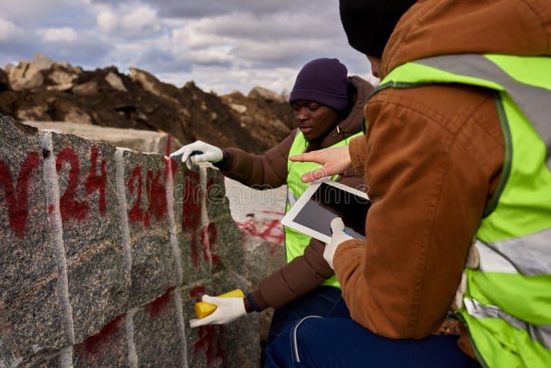 Twee Arbeiders die Granit merken stock afbeelding