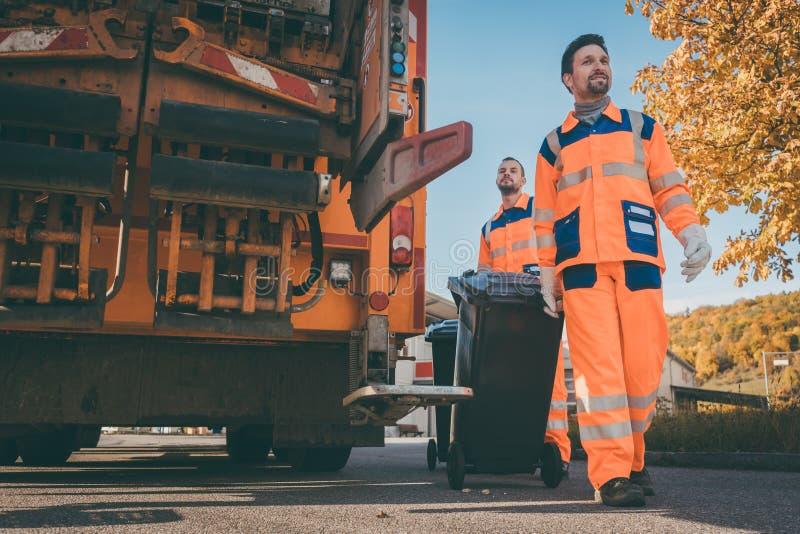 Twee arbeiders die van de afvalinzameling huisvuil laden in afvalvrachtwagen stock fotografie